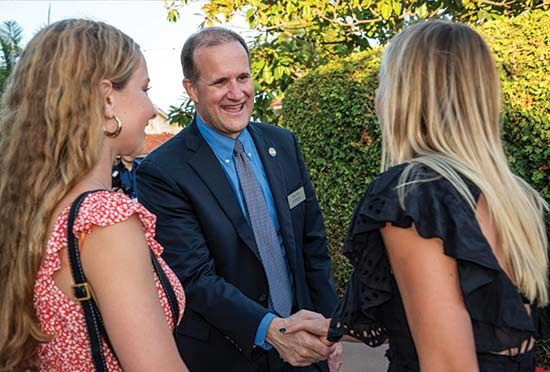 President Gash shaking hands with two students outside