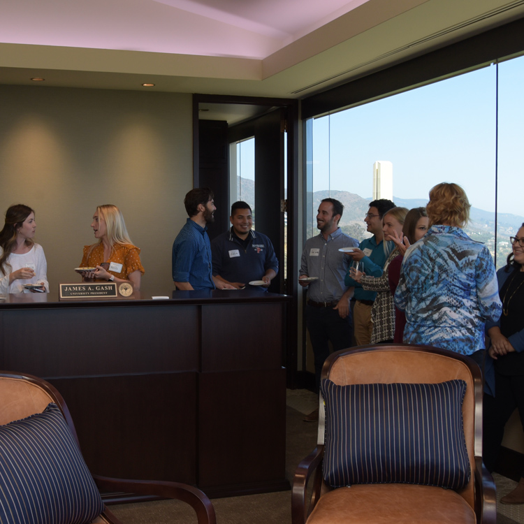 Staff members mingle in the president's suite
