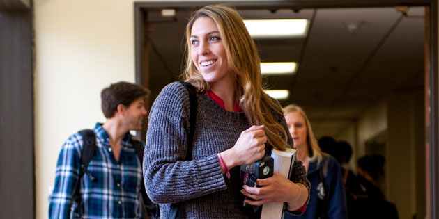 A student holding books smiles in the hallway - Pepperdine University