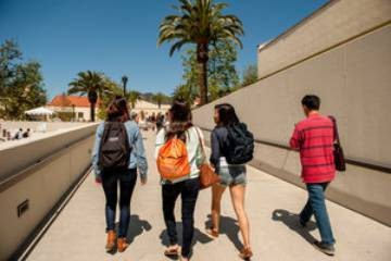 Students with backpacks walk through campus - Pepperdine University