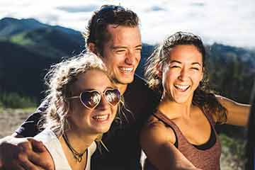 Seaver College students smiling at the top of a mountain