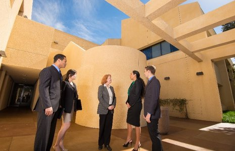 Students in business suits talk on campus - Pepperdine University