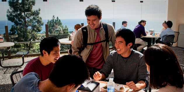 A group of Asian male students laugh together at Waves Cafe - Pepperdine University