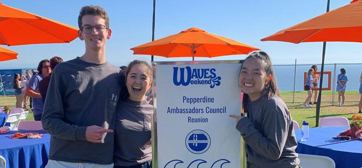 PAC students photographed in front of a sign at Waves Weekend.