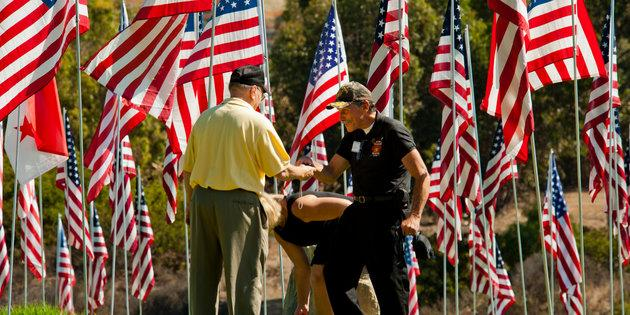 two veterans shake hands in front of 9/11 flag memorial at Pepperdine.