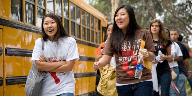 Female students walking next to a school bus