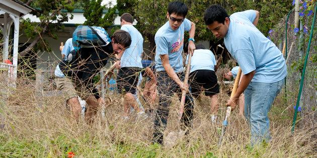 Male students raking leaves during Pepperdine University's Step Forward Day