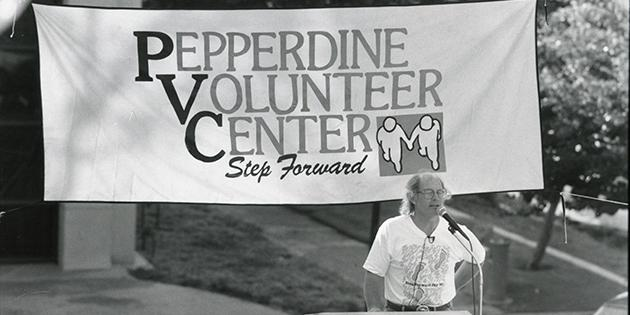 A man speaking at a podium at Pepperdine University's Step Forward Day