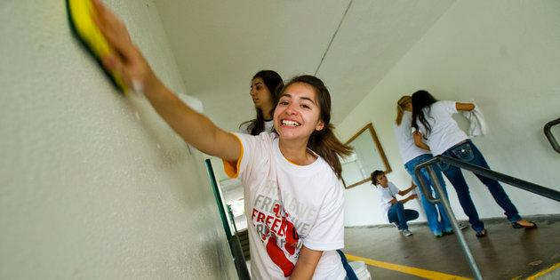 Female student scrubbing the wall