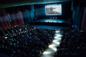 Large auditorium with movie playing