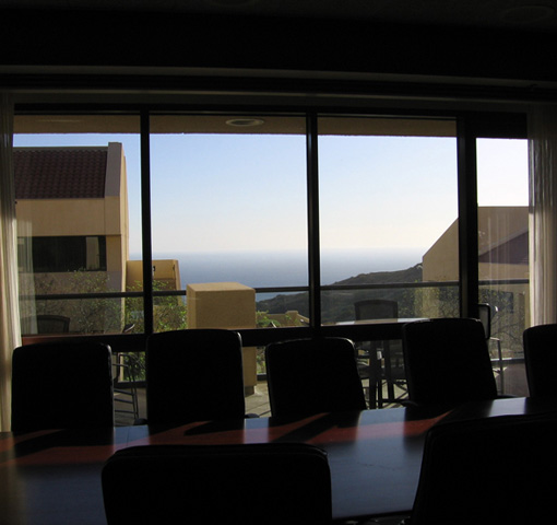 GSBM Dean's conf. rm., silhoutted against glass wall/oceanview
