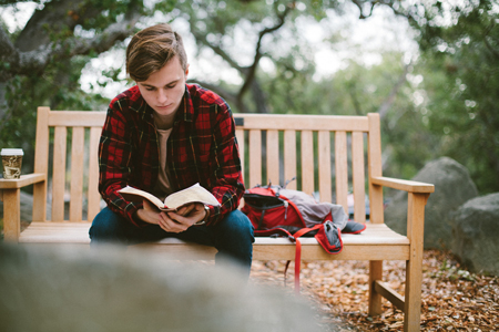 Student Reading Bible on Bench