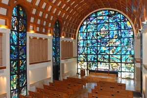 Stauffer Chapel is empty with light shining through the stained glass wall - Pepperdine University