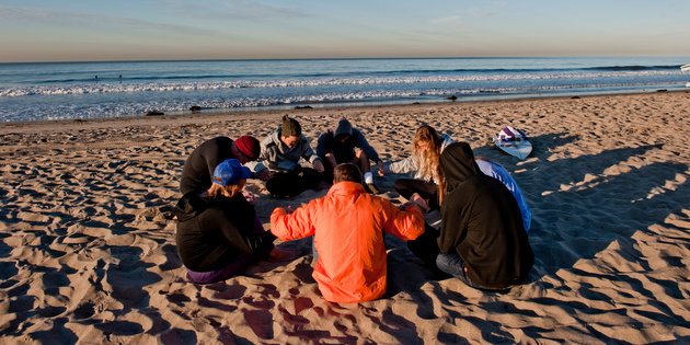 Students pray on the beach - Pepperdine University